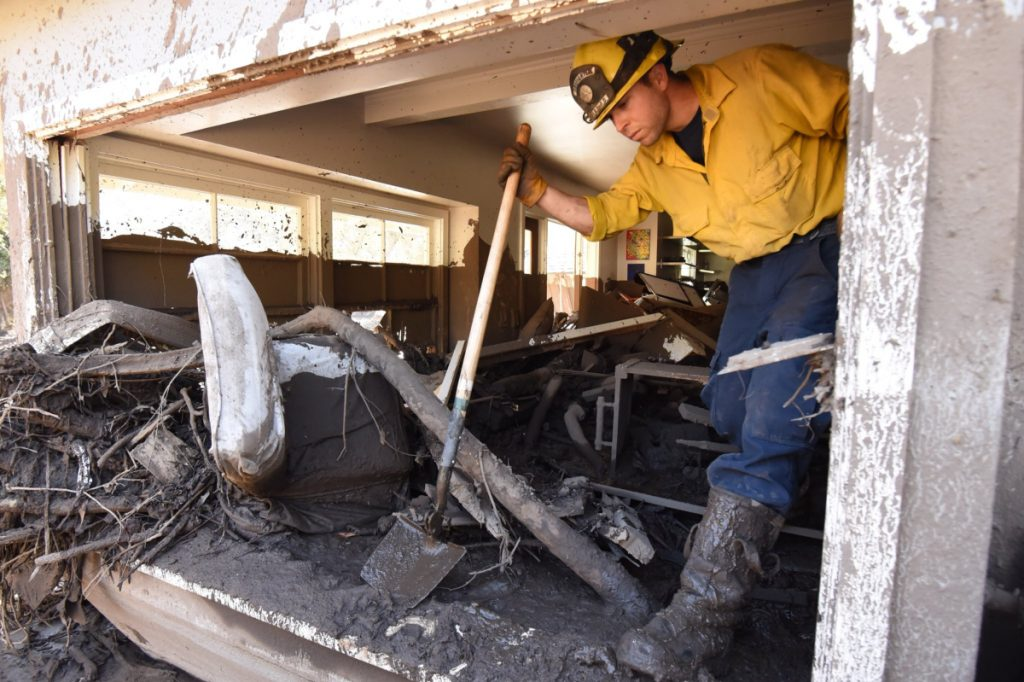 Santa Barbara County firefighter Vince Agapito climbs through a Montecito, Calif., home Saturday that was destroyed by deadly mudflow and debris early Tuesday morning following heavy rainfall. (Mike Eliason/Santa Barbara County Fire Department via AP)