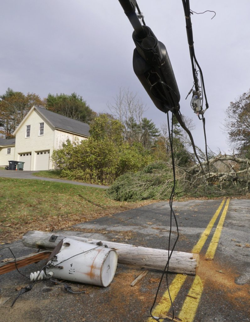 A pole with a transformer attached lies on Flying Point Road in Freeport, under wires weighted down by trees on Nov. 3.
