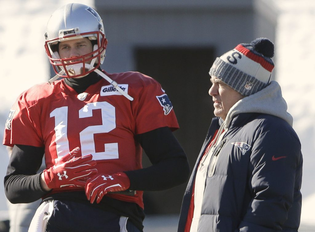 Standing with Coach Bill Belichick, right, on Thursday, Tom Brady wears a glove on his right hand, an unusual development with Brady sitting out another practice with a hand injury.