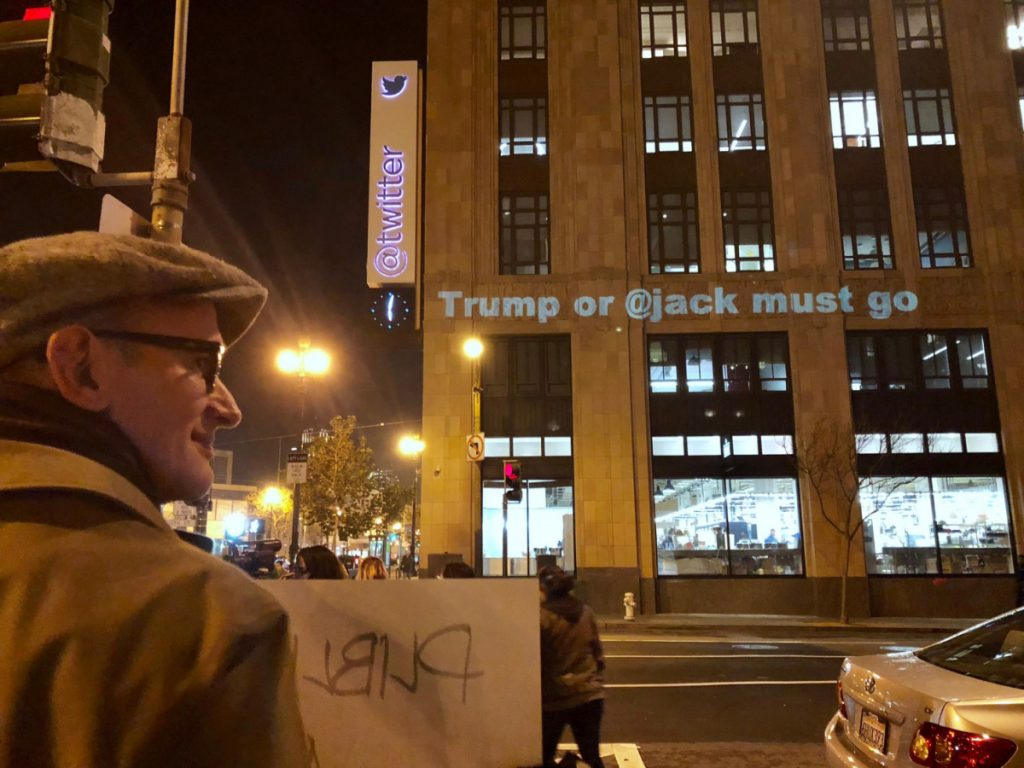 Protesters gather outside Twitter's headquarters in San Francisco, and project messages on the building.