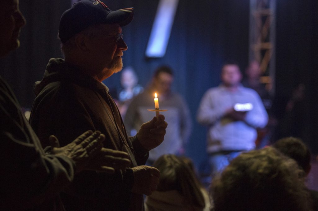 Stan Collins, of Benton, second from left, holds a candle during a vigil at Impact Church in Benton, Kentucky, on Tuesday for victims of the Marshall County High School shooting earlier in the day.
