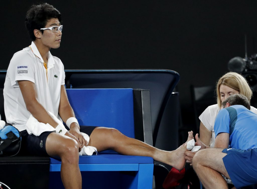 South Korea's Hyeon Chung receives treatment from a trainer during his semifinal against Roger Federer at the Australian Open.
