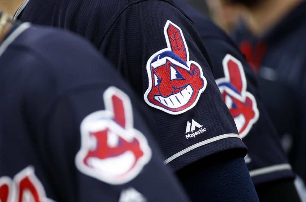 Members of the Cleveland Indians wear uniforms featuring mascot Chief Wahoo as they stand on the field for the national anthem before a game against the Orioles in Baltimore. Cleveland is taking the divisive Chief Wahoo logo off their jerseys and caps, starting in 2019.