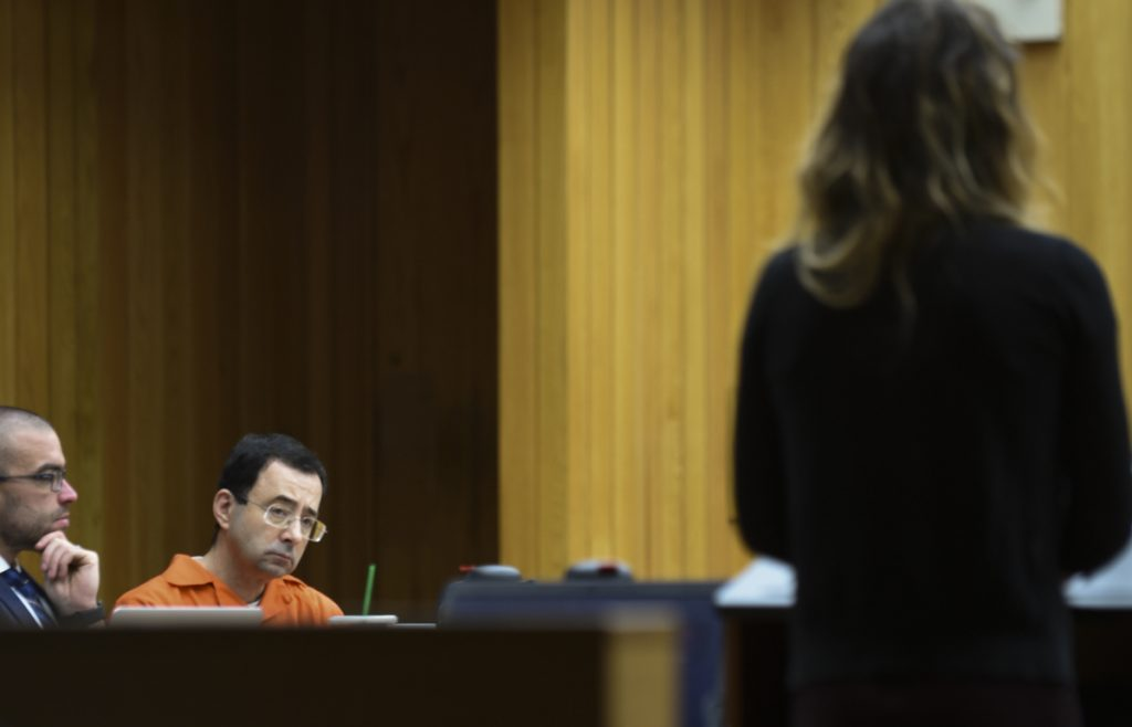 Larry Nassar, second from left, listens as a woman gives her victim impact statement Wednesday in Eaton County Circuit Court in Charlotte, Mich.