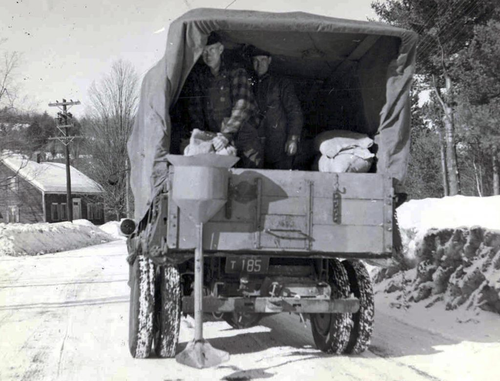 This 1940s photo shows salt being applied for de-icing on a New Hampshire road. Today, New Hampshire and Maine use a mixture that includes molasses. Research shows that rock salt corrosion harms water ecosystems.