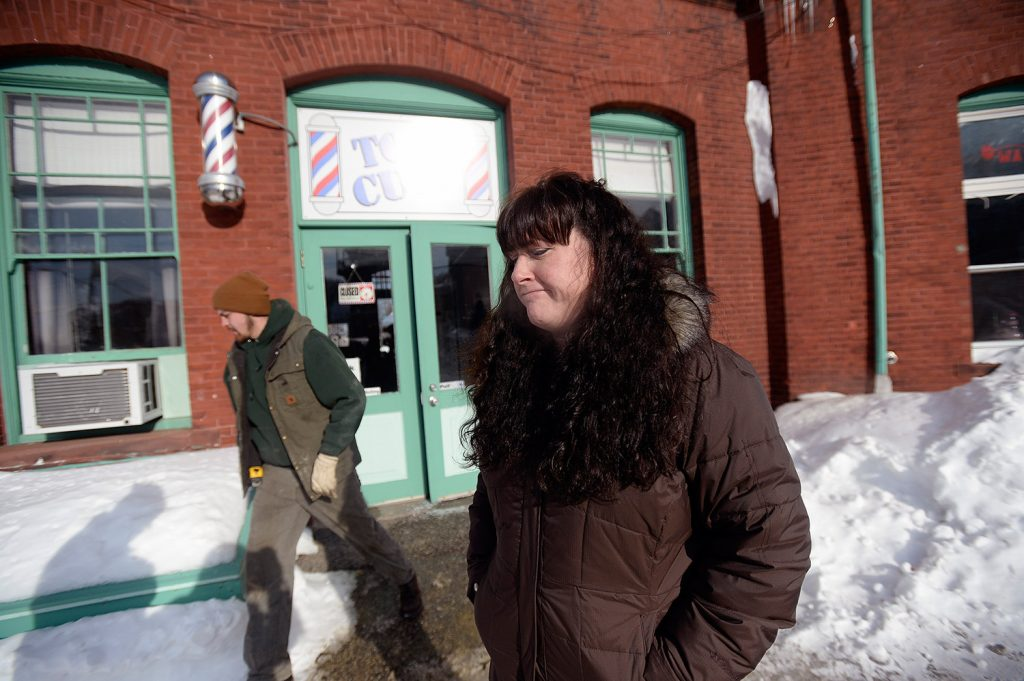 Ginny Ayers, owner of Top Cuts Barber Shop, stands outside the shop Tuesday after pipes in the building burst because of the frigid temperatures.