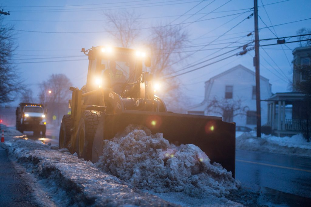Portland city workers clear softened snow off the side of Presumpscot Street on Friday evening. Crews worked to get snow moved off roadsides, with colder temperatures and a messy winter storm on the way.