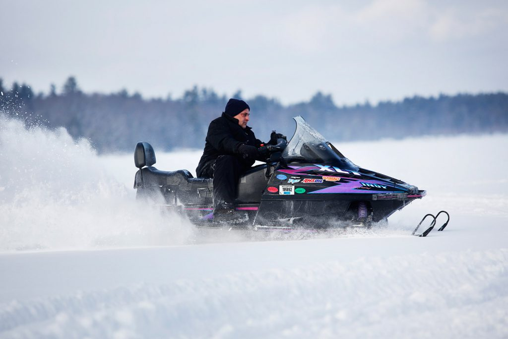 "Buddy Keenan of Somerville, Mass., rides a snowmobile Friday at Lower Bay on Sebago Lake. Maine game wardens are warning about ""very hazardous"" ice conditions created by recent warm weather."
