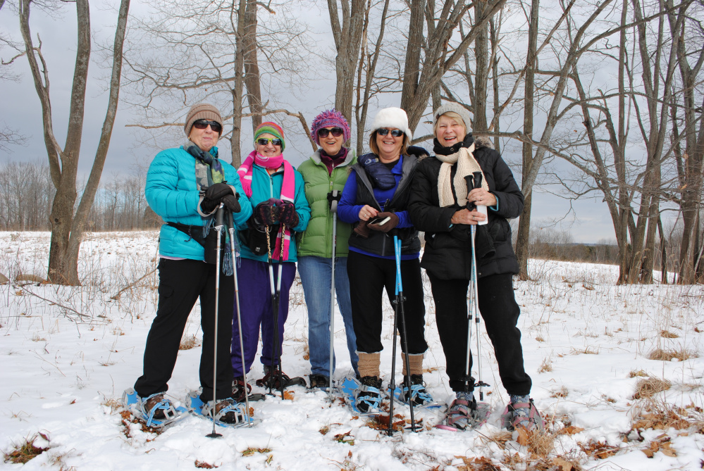 A group of women take a break from snowshoeing at Viles Arboretum in Augusta.