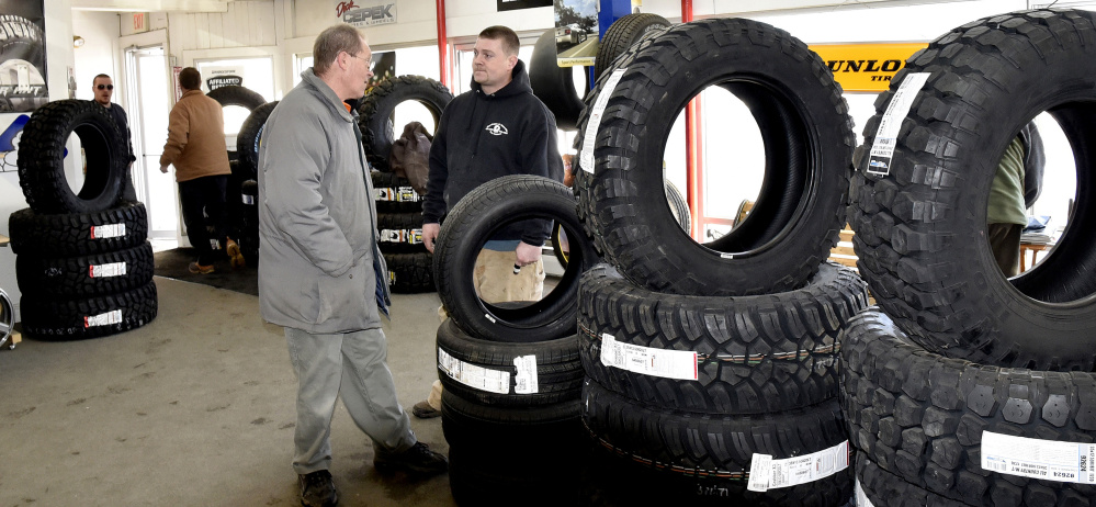 Waterville Tire Warehouse Manager Mike Savage, right, speaks with customer Dan Bernier on Tuesday at the busy company in Waterville. Savage said the recent cold weather has caused a spike in the company's tire repair business.