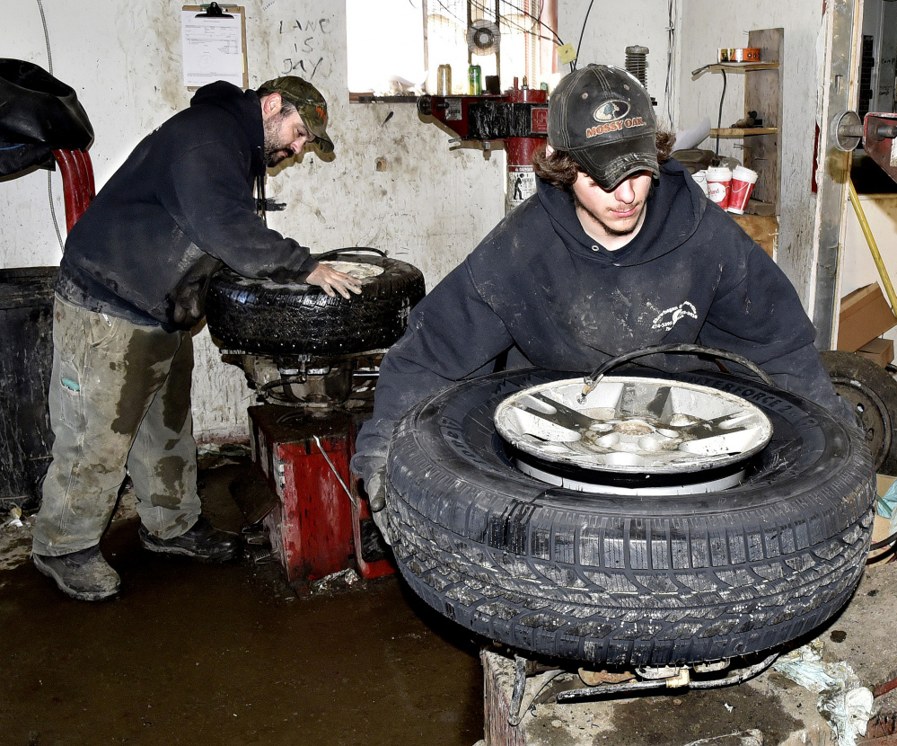 Waterville Tire Warehouse employees Jason Dumais, left, and Lane LeBlanc change tires Tuesday at the company store in Waterville. LeBlanc said their work has been nonstop because the cold weather is causing tires to deflate, and people are installing snow tires.