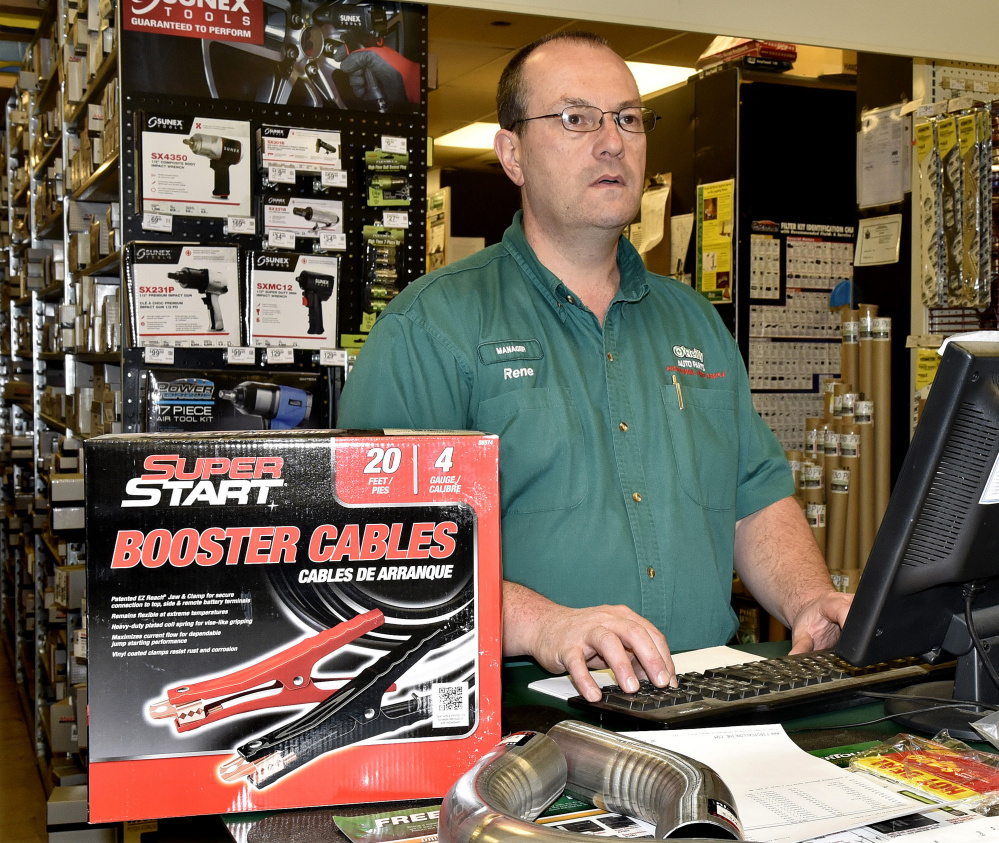 O'Reilly Auto Parts store manager Rene Huard waits on a customer purchasing battery booster cables Tuesday at the Waterville store. Huard said the store has sold 70 batteries since the weekend and a truckload is arriving this week.