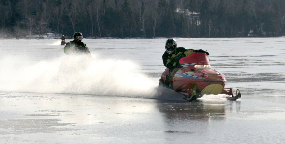 Snowmobilers plow through six inches of water on top of frozen Rangeley Lake during the Snodeo in Rangeley last year.