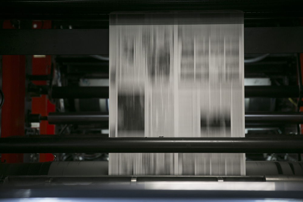 Newsprint runs through the printing cylinders of a newspaper press at The Washington Post production facility in Springfield, Virginia, on July 12, 2013. (Andrew Harrer/Bloomberg)