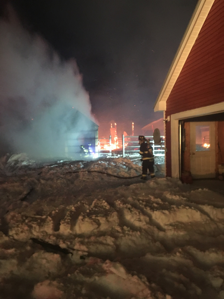 A firefighter battles a blaze that destroyed a barn and an outbuilding that belong to Starks Selectman Paul Frederic during a blizzard Thursday night on Chicken Street in Starks.