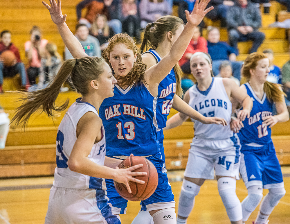 Mountain Valley's Brooke Carver, front, looks for a teammates Oak Hill's Desirae Dumais defends during Friday night's game in Rumford.