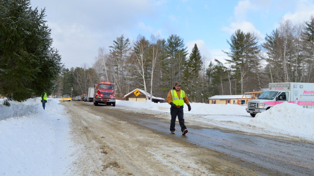 Members of the Temple Fire Department stop traffic Tuesday morning from the Temple Town Office to the post office on Route 43. State police vehicles line the road while troopers investigate a shooting incident in which two people died.