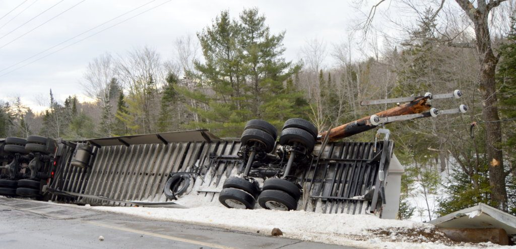 A mangled utility pole and wires lie atop a flipped tractor-trailer Thursday on Route 27 in New Vineyard. The Utah driver was distracted while looking for directions to the Interstate.