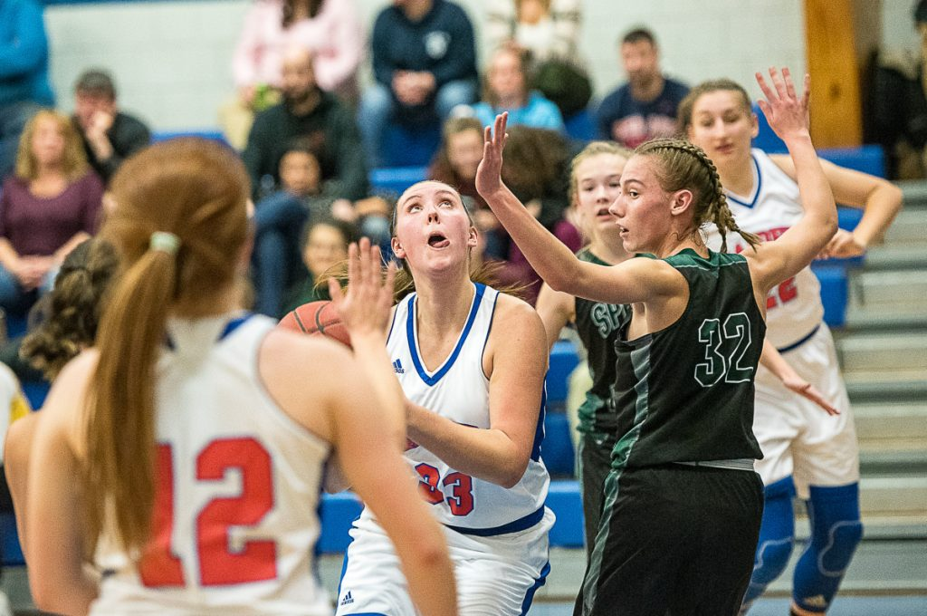 Sun Journal photo by Andree Kehn   Oak Hill's Abigail Nadeau concentrates on getting a shot past Spruce Mountain's Calley Baker during a game Thursday night in Wales.