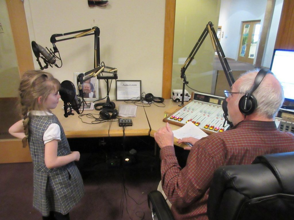 St. John's Catholic School first-grade student Riley Shean gets ready to speak on the radio for the first time. Jim Bleikan, of Radio 9 WCME, is at right.