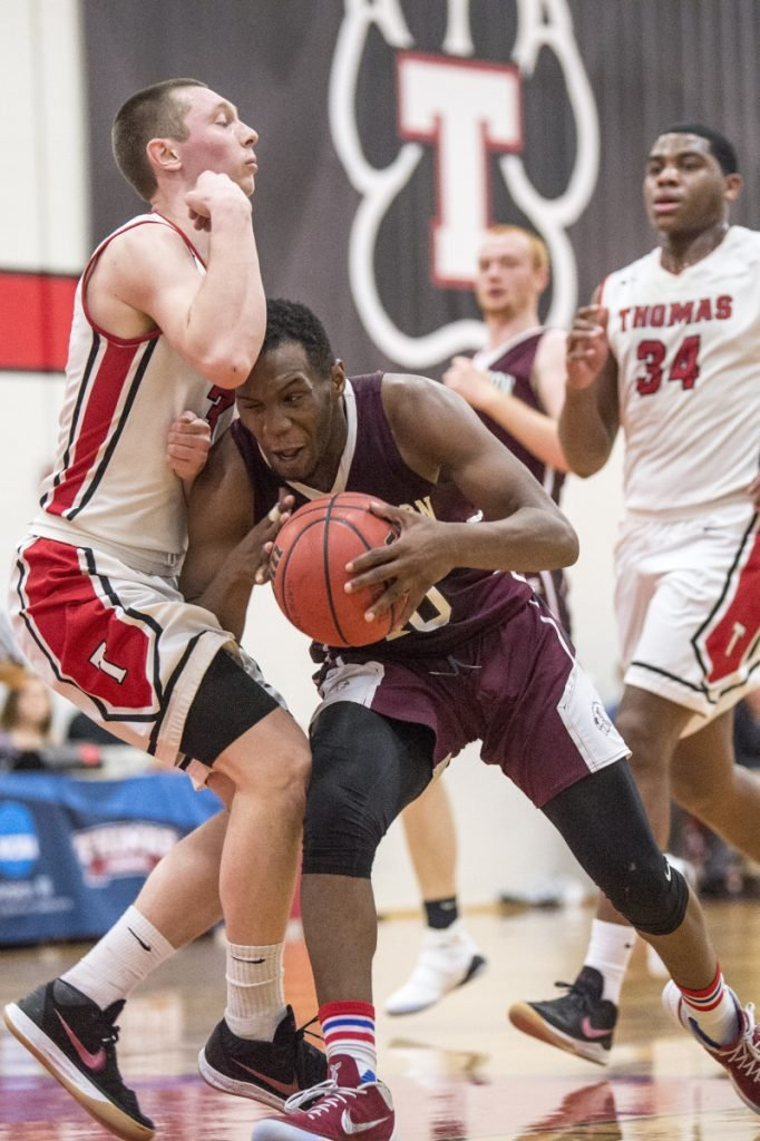 University of Maine at Farmington's Amir Moss, right, is called for an offensive foul as he plows through Thomas College's Zach Mackinnon on Saturday at Thomas College in Waterville.