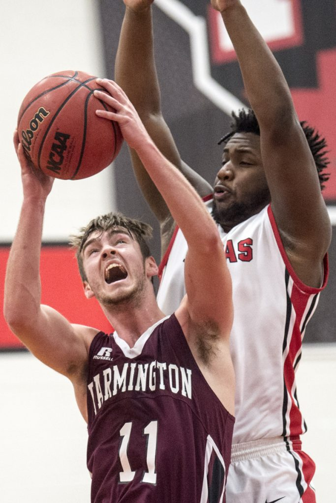 University of Maine at Farmington's Isaac Witham (11) draws the foul from Thomas College's Justin Butler (14) on Saturday at Thomas College in Waterville.