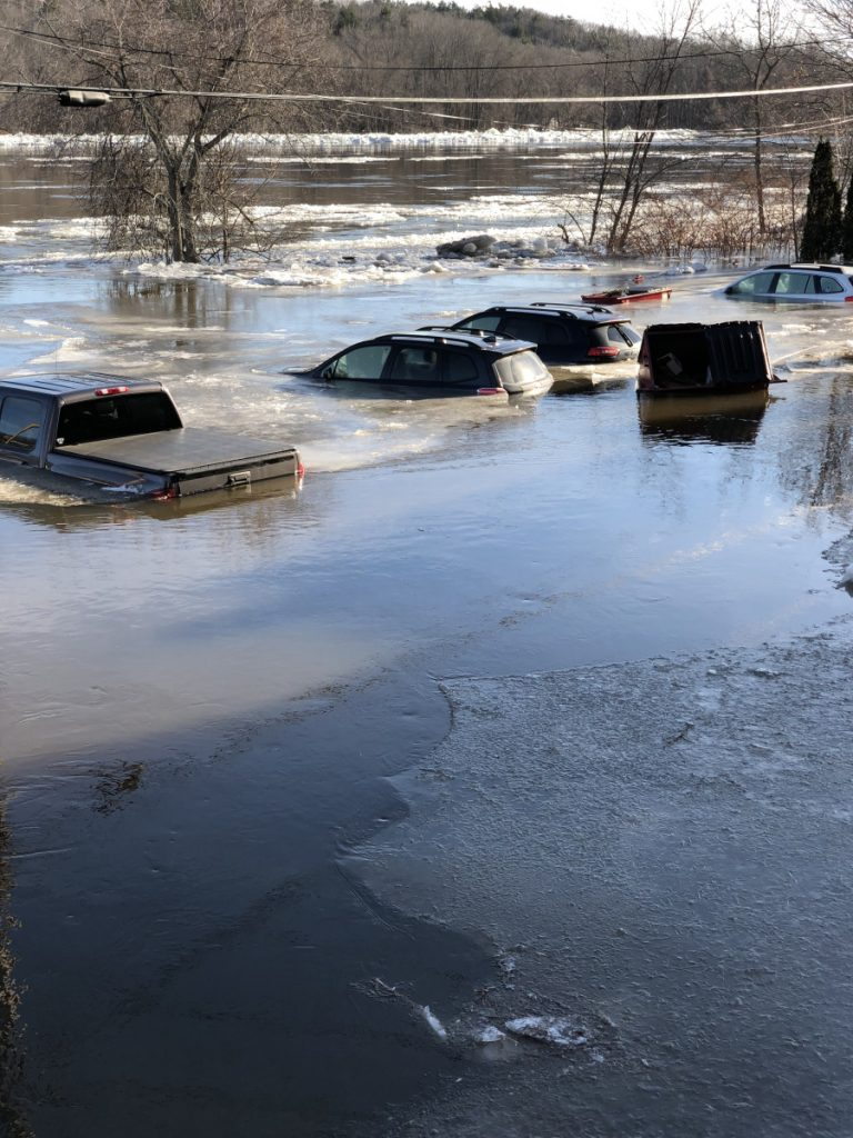 Cars submerged by flooding Kennebec River on Sunday in Hallowell.