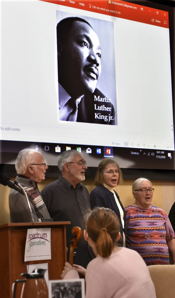 Members of the Tourmaline Singers sing under a projected image of Martin Luther King Jr. during the 32nd annual Martin Luther King Jr. Community Breakfast at the Muskie Center in Waterville on Monday.