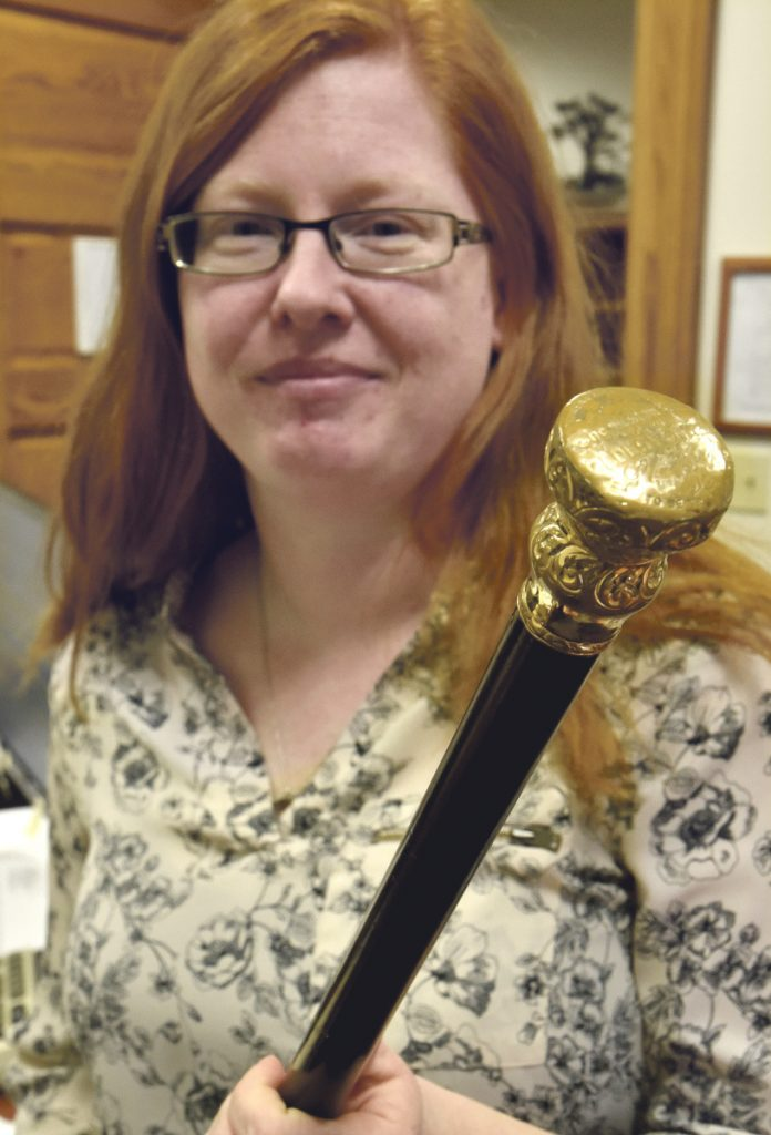 Skowhegan Town Manager Christine Almand holds the gold-topped ebony Boston Post Cane at the town office in Skowhegan on Monday. The last time the town's eldest citizen received the cane was in 1999, according to research done by Town Clerk Gail Pelotte. Efforts are underway to restore the New England tradition.