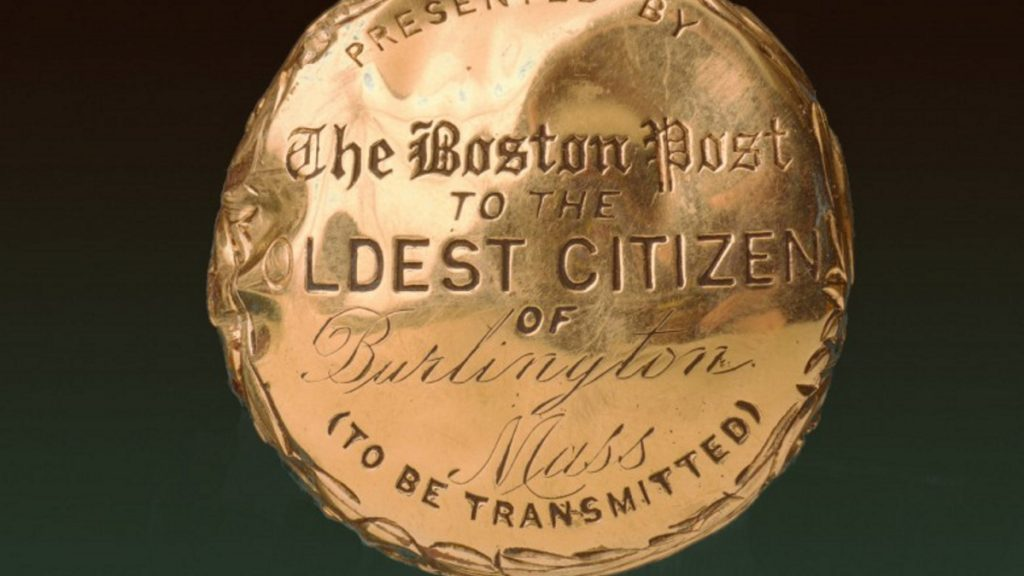 "The inscription on the 14 carat gold head of the cane reads ""Presented by the Boston Post to the oldest citizen of (name of town) — (To Be Transmitted)."""