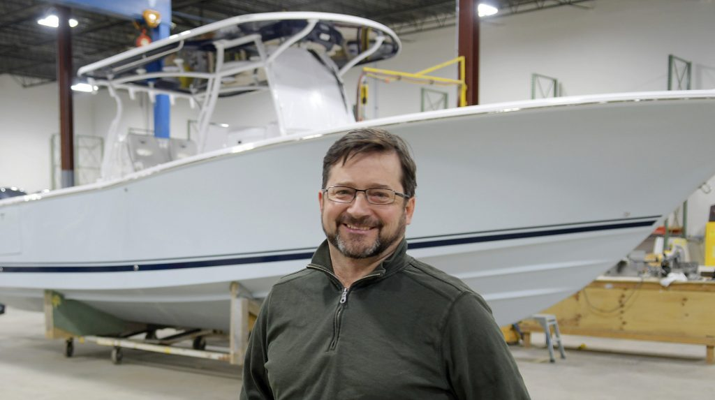 Southport Boats chief operating officer George Menezes with a 33-foot model of the vessel the firm manufactures at their new facility in Gardiner on Monday. Southport Boats, formerly part of Augusta's Kenway Corp., has relocated to Gardiner under new ownership and will continue to produce its line of center console fishing boats there.