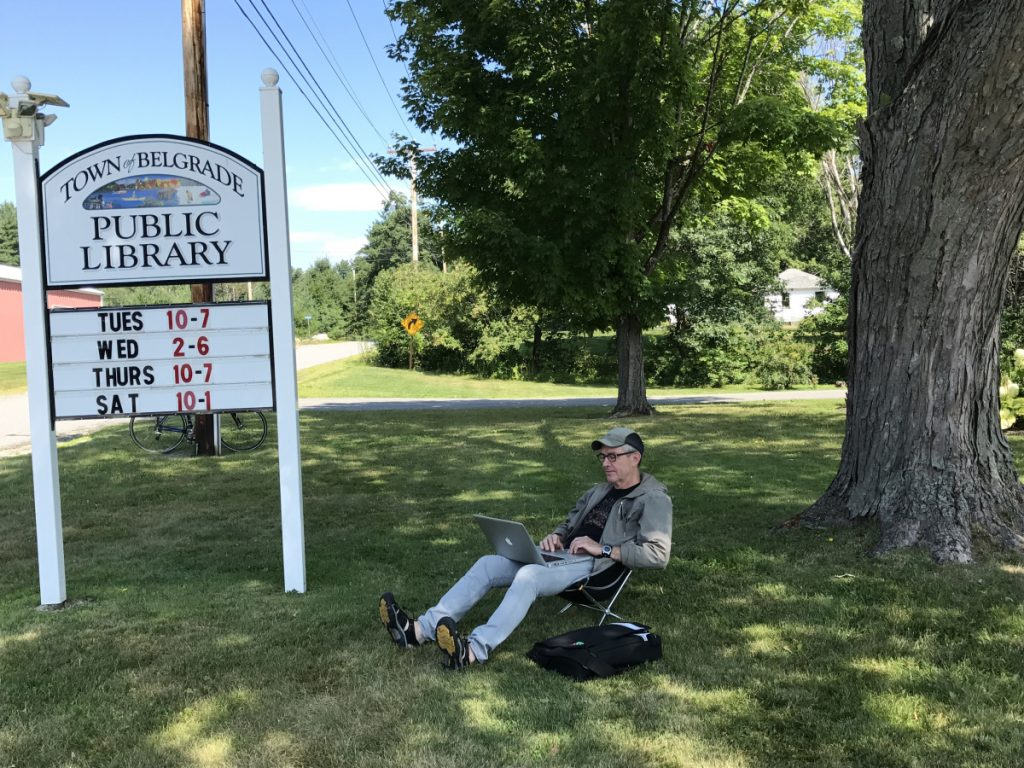 Robin Budd, a tourist visiting from Toronto, Ontario, finds a shady spot under a tree Aug. 9, 2017, at the Belgrade Public Library on Depot Road. Town voters will decide at the upcoming Town Meeting whether the library should have a full-time director.