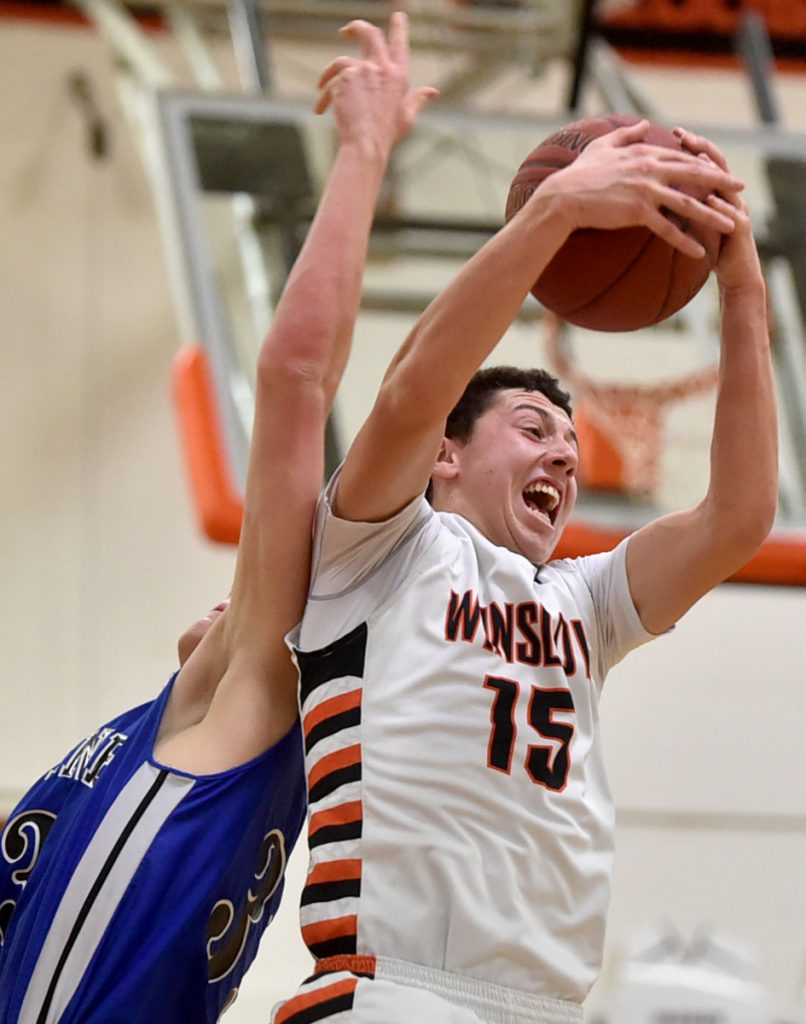 Winslow's Jack Morneault (15) grabs a rebound in a game against Erskine last season. Morneault and the Black Raiders are 8-3 and in fourth place in Class B North.