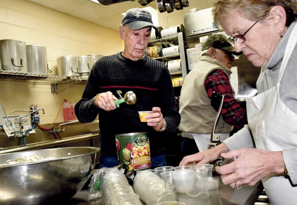 Roger Derosier, Dot Marshall and other volunteers prepare meals Monday for the Meals on Wheels program at the Muskie Center in Waterville.