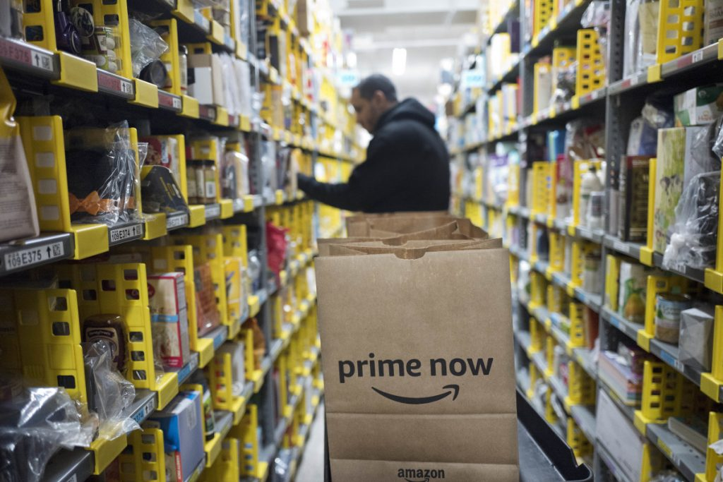 In this Wednesday, Dec. 20, 2017, file photo, A clerk reaches to a shelf to pick an item, Dec. 20, 2017 for a customer order at the Amazon Prime warehouse, in New York. Amazon announced Thursday that it has narrowed down its potential site for a second headquarters in North America to 20 metropolitan areas, mainly on the East Coast.