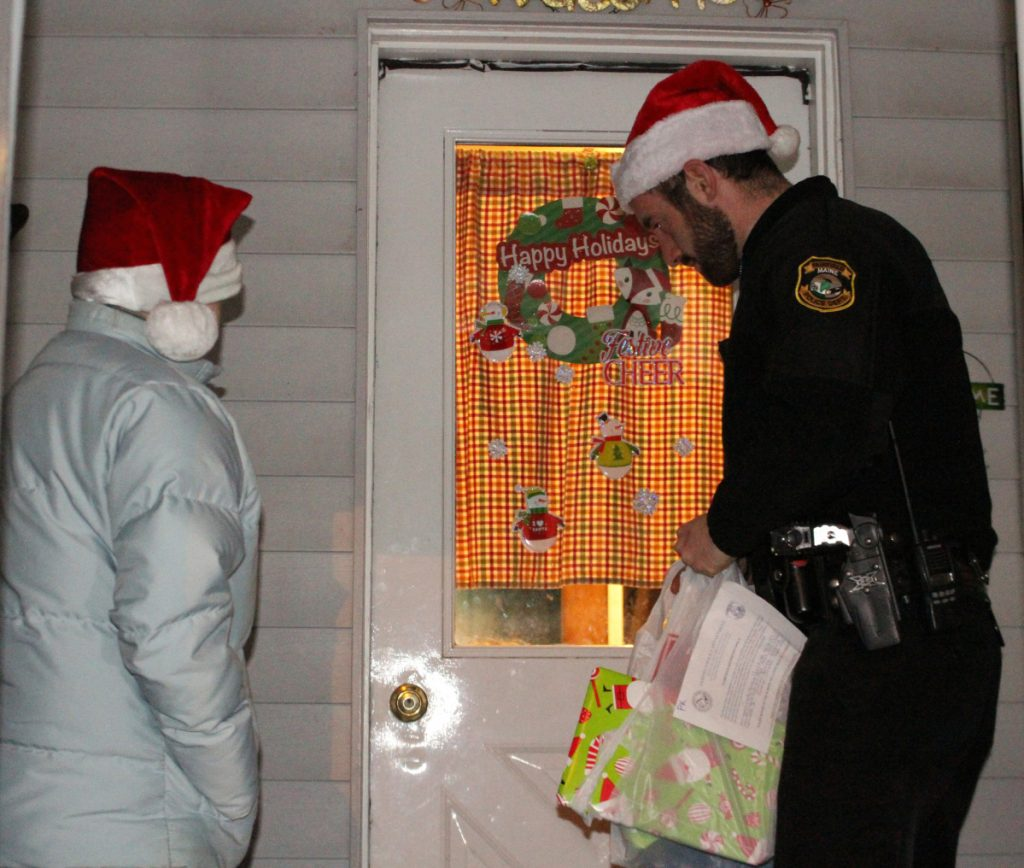 Dispatcher Jeanne Kempers, left, with Officer Blake Wilder, recently deliver gifts to children in a Fairfield home.