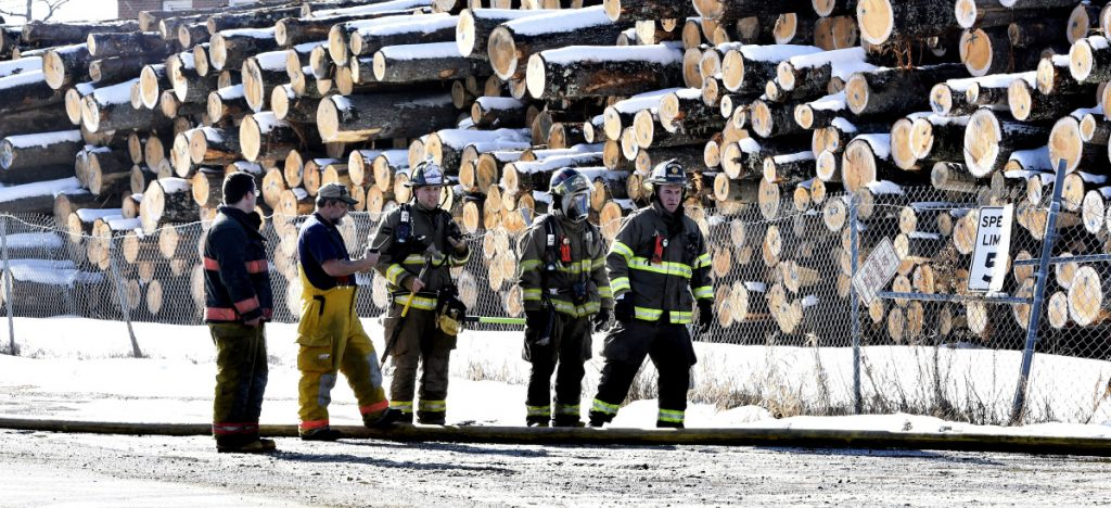 Firefighters from several area departments congregate outside the Hancock Lumber company to assist putting out a fire at the mill in Pittsfield on Sunday.