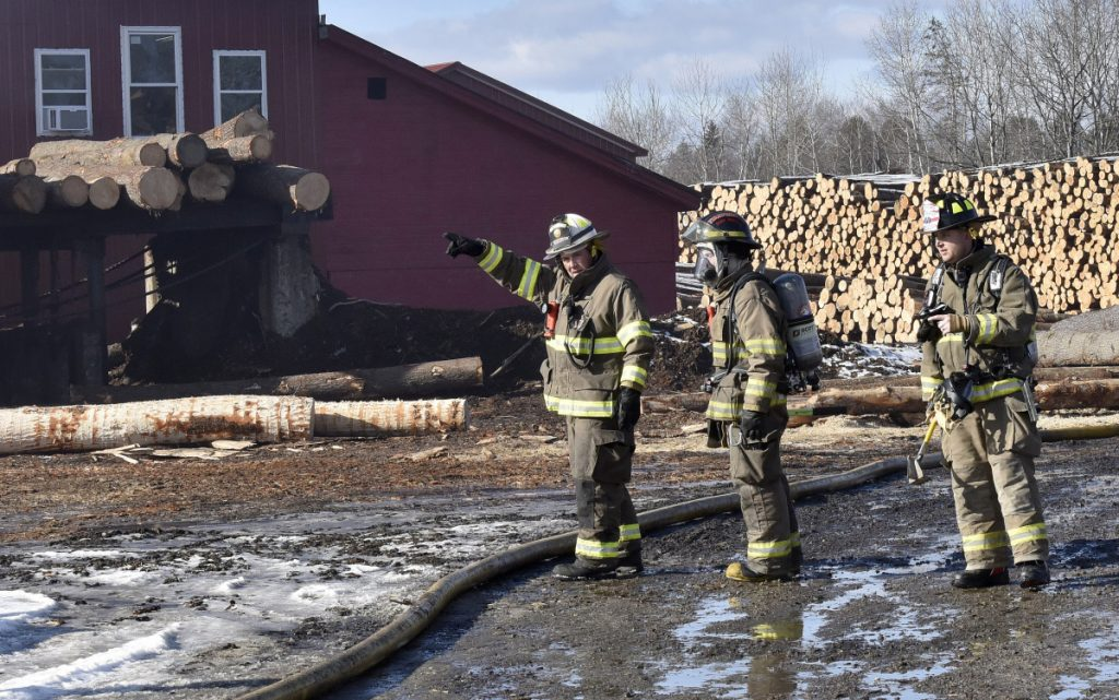 Firefighters convene at one end of the Hancock Lumber company sawmill building in Pittsfield where fire was reported on Sunday.