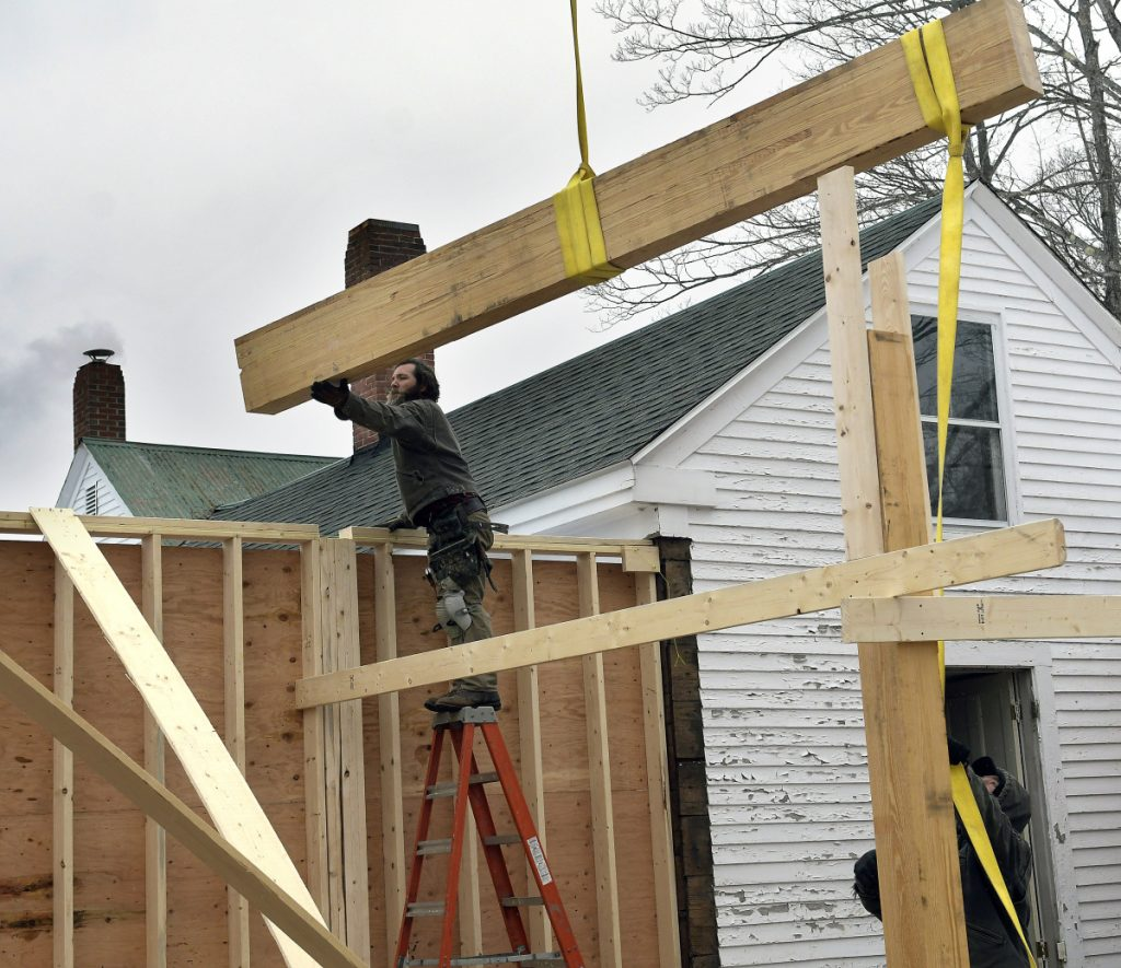 Workers set a roof beam on Monday for the expansion of the Dr. Shaw Memorial Library in Mount Vernon.