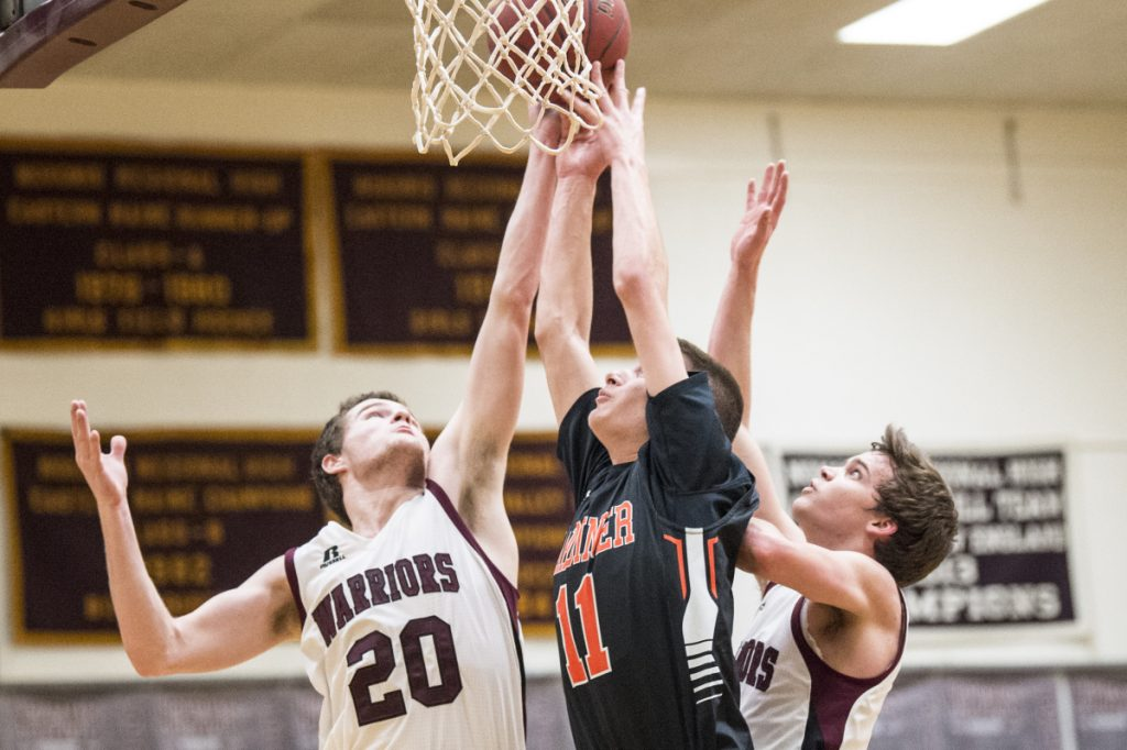 Gardiner's Logan Carlton, center, battles for the rebound with Nokomis' Zach Hartsgrove, left, and Josh Smestad during a Kennebec Valley Athletic Conference Class A game Thursday night in Newport.