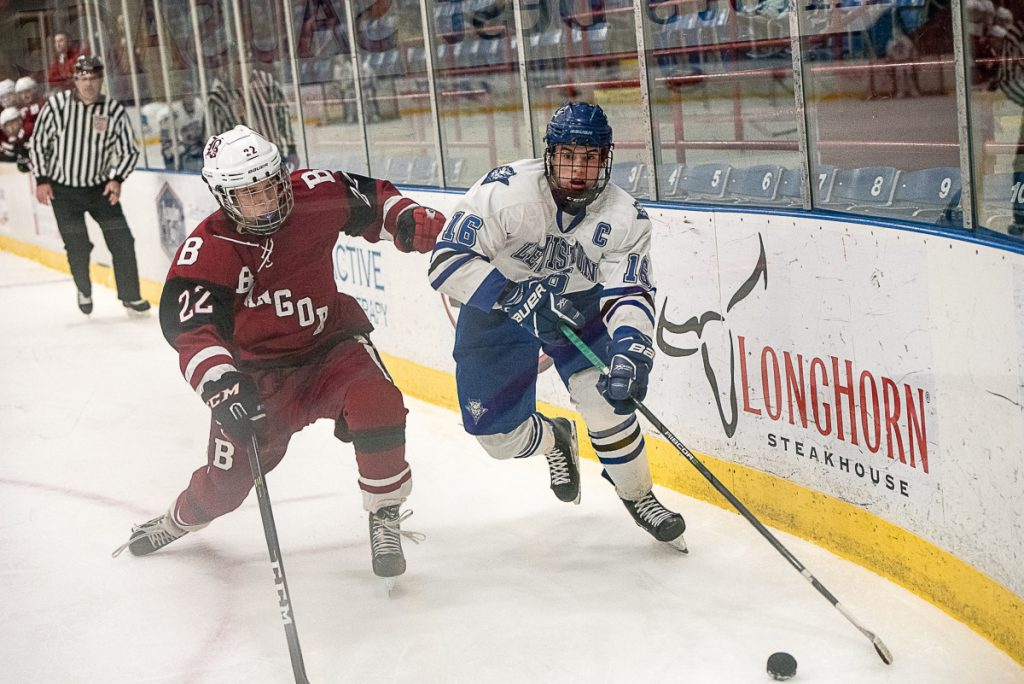 Bangor's Anthony Caccese and Lewiston's Alex Robert struggle for control of the puck during a Class A North game Friday night in Lewiston.