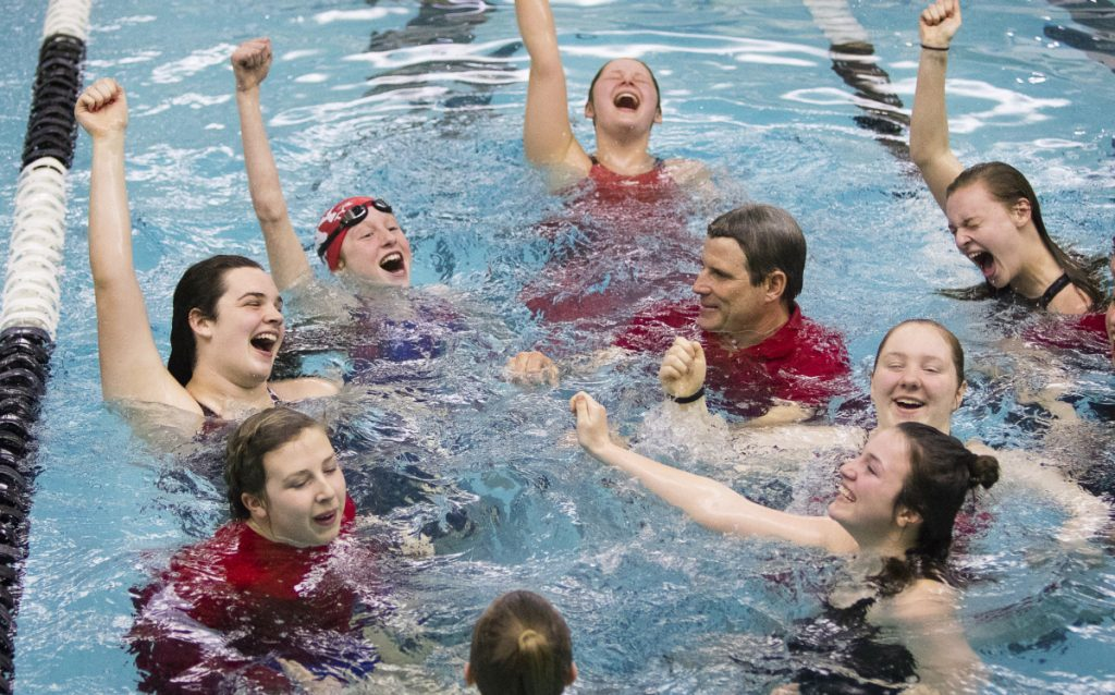 Members of the Cony girls swim team, including coach Jon Millett, take a celebratory swim after winning the Class A state championship last season at Bowdoin College in Brunswick.