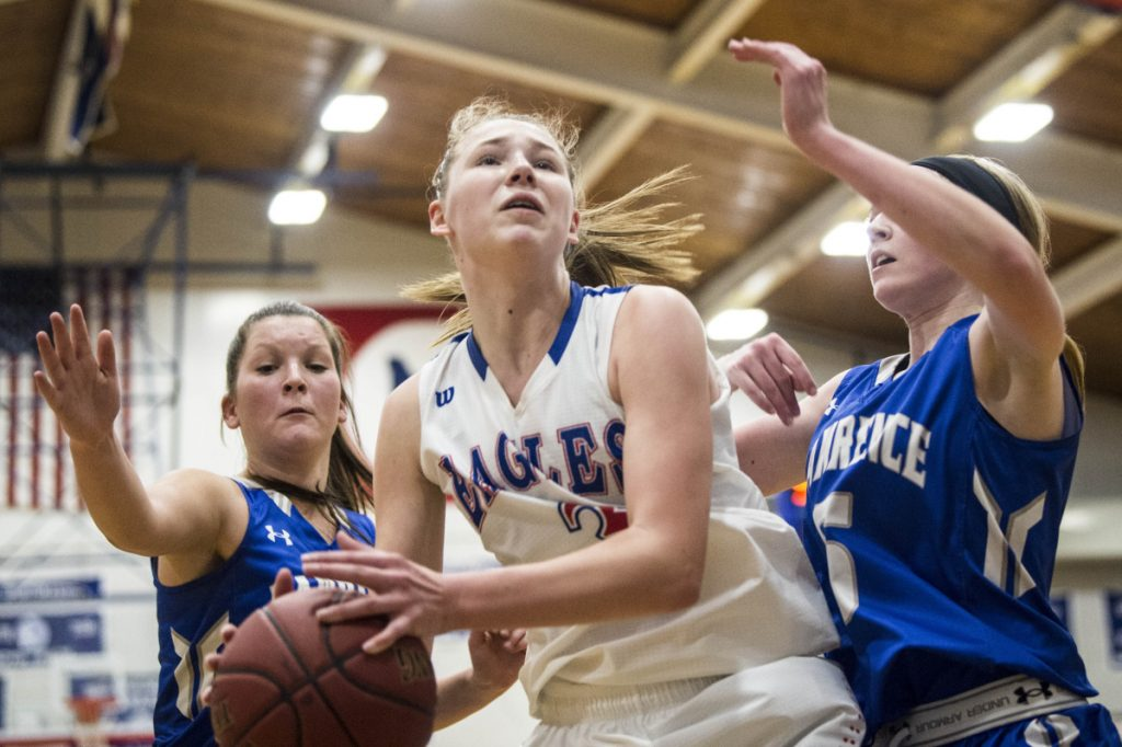 Messalonskee sophomore Gabrielle Werner (3) grabs a rebound as  Lawrence defenders Brooklynn Lambert, right, and Lexi Lewis close in  during a Kennebec Valley Athletic Conference Class A game Wednesday night in Oakland.