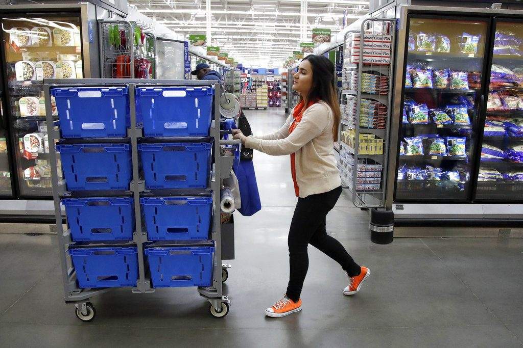 Laila Ummelaila, a personal shopper at the Walmart store in Old Bridge, N.J., pushes a cart with bins as she shops for online shoppers, in November. On Thursday, Walmart announced it is boosting its starting salary for U.S. workers to $11 an hour.