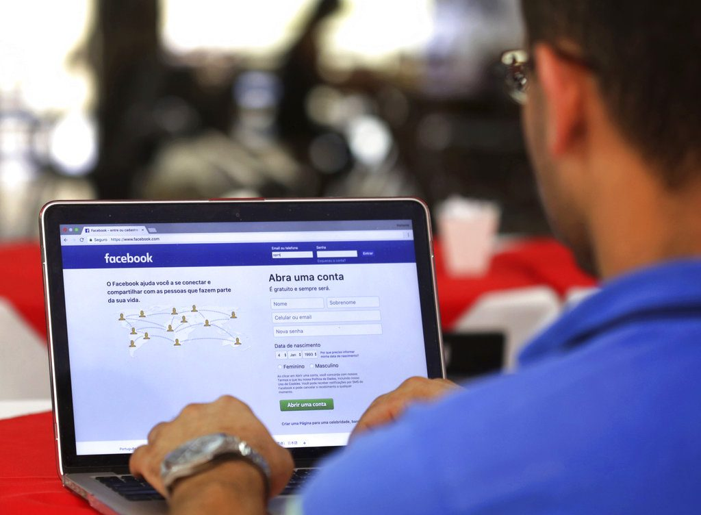 In this Thursday, Jan. 4, 2018, file photo, a man demonstrates how he enters his Facebook page as he works on his computer at a restaurant in Brasilia, Brazil. Facebook is once again tweaking the formula it uses to decide what people see in their news feed to focus more on personal connections and take the spotlight off brands and news articles. (AP Photo/Eraldo Peres, File)