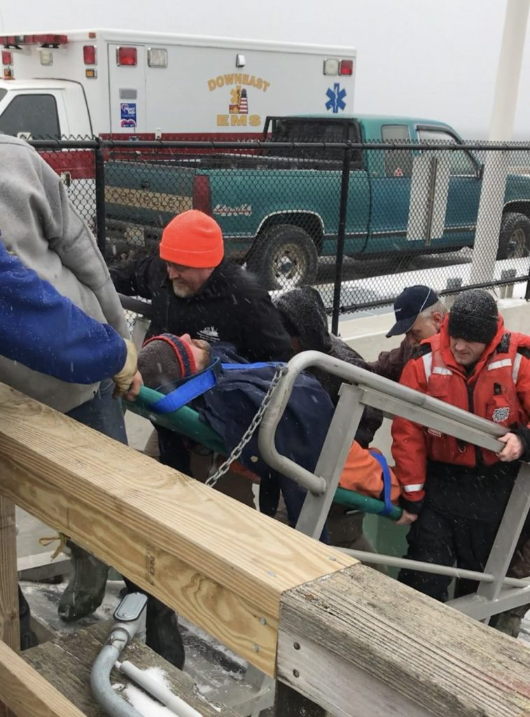 A U.S. Coast Guard crew transfers one of four people rescued after their 14-foot skiff capsized in Deep Cove near Eastport on Tuesday.