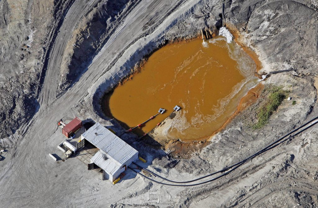 Water flows into a tailings pond at the Suncor Energy oil sands mine in this aerial photograph taken near Fort McMurray in Alberta, Canada, on June 4, 2015.