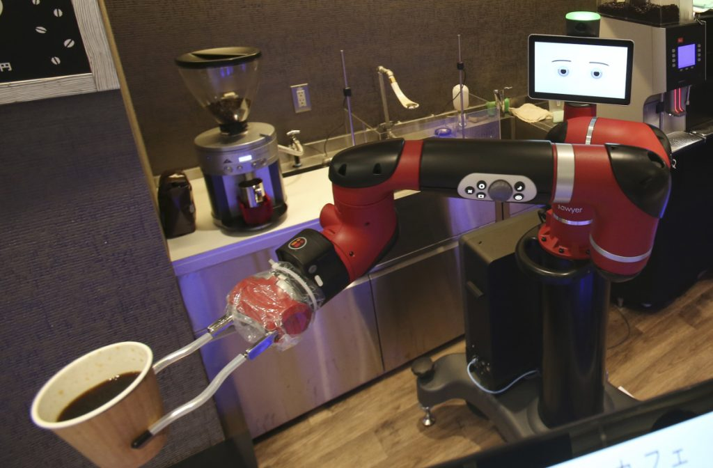 "Sawyer, a robot barista, makes a coffee at Henn-na Cafe in Tokyo on Friday. ""I can make one better than human beings around here,"" the robot says."