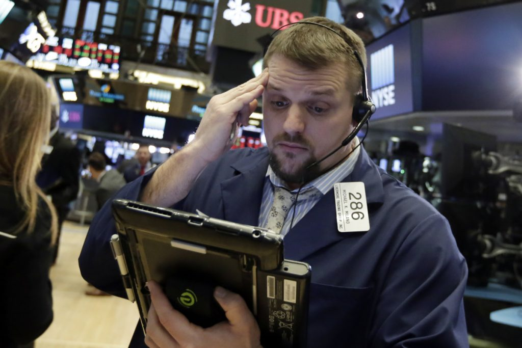 Trader Michael Milano works on the floor of the New York Stock Exchange on Tuesday, when markets were volatile.