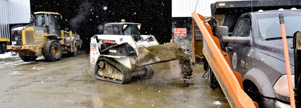 Larry Colsen fills a Waterville Public Works plow truck with sand as Mike Folsom uses a bucket loader to fill another truck Tuesday at the department in anticipation of Wednesday's snowstorm.